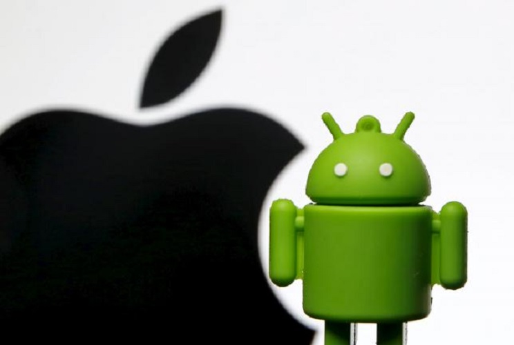 Android mascot is seen in front of a displayed logo of Apple in this photo illustration taken in Zenica